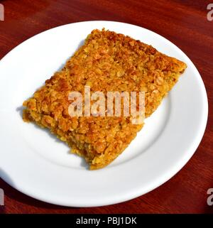 Flapjack on a white plate - Stock Photo