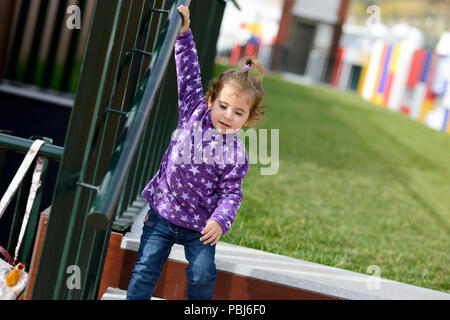 Little 20-month-old girl going down some stairs outdoors - Stock Photo