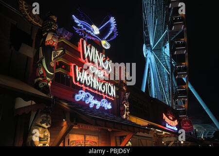 Seattle, Washington - June 30, 2018 : Pier 57 at night with neon signs of tourist businesses and of Great Ferris Wheel in Seattle, WA. Seattle's water - Stock Photo