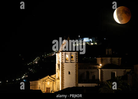 Double exposures of the red blood moon over the Cáceres old town - Stock Photo