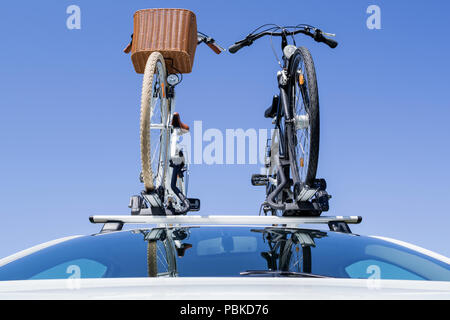 bicycle rack on top of white car - Stock Photo