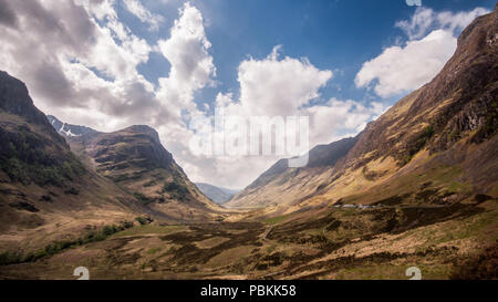 The iconic steep sided valley of Glen Coe is cuts between the rugged mountains of Bidean nam Bian and Am Bodach in the Highlands of Scotland. - Stock Photo
