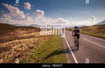 Fort William, Scotland, UK - May 22, 2010: Mountainbikers ride through the wilderness landscape of Rannoch Moor on the A82 road in the Highlands of Sc - Stock Photo