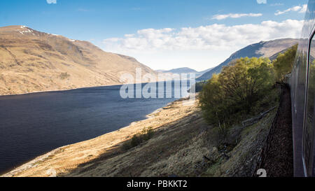Loch Treig reservoir under mountains of the Nevis massif in the West Highlands of Scotland, as viewed from the West Highland Line railway. - Stock Photo