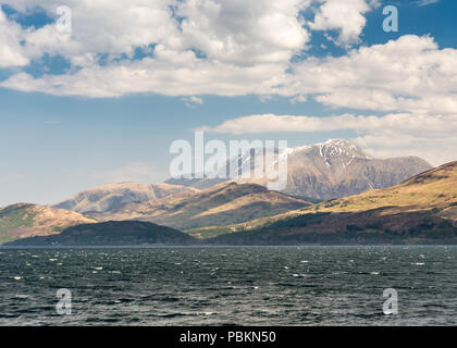 Snow lies on the summit of Ben Nevis mountain as it rises from the shores of Loch Linnhe sea loch in the West Highlands of Scotland. - Stock Photo