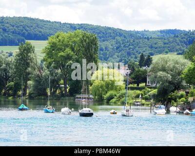 Boats on alpine Rhine River in swiss canton Schaffhausen near european STEIN am RHEIN town landscape in Switzerland with cloudy blue sky in 2017 warm  - Stock Photo