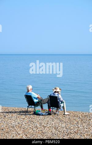 Elderly white couple sitting on the beach at Hastings on a hot summers day, East Sussex England UK - Stock Photo