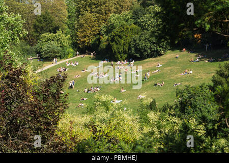 Paris park - Top view of people enjoying hot summer afternoon on the slope of Parc des Buttes Chaumont in Paris, France. - Stock Photo