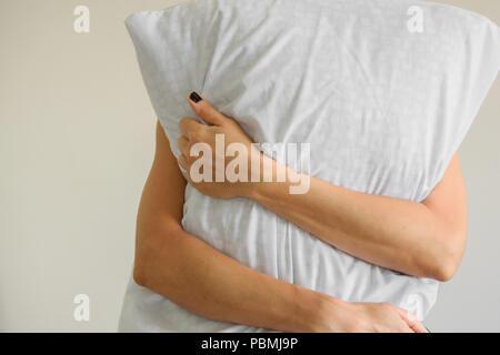 Close up of womans hands hugs a pillow - Stock Photo