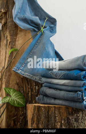Pairs of jeans hanging on an old wooden trunk, white background with copy space - Stock Photo