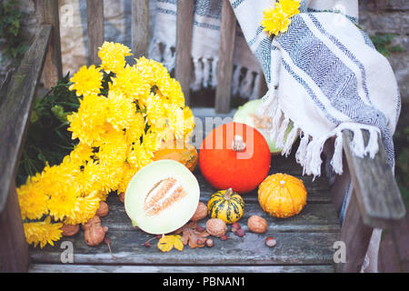 Autumn nature. Fall fruit on wood. Thanksgiving. autumn vegetables on an old chair in the garden, free space for text, yellow flowers - Stock Photo