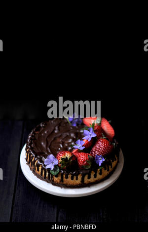 chocolate cake with berries on a black background. sweet homemade pastries - Stock Photo