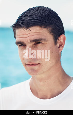Close-up portrait of one white Caucasian  man with dark small eyes and short hair looking away outside by water sea on beach - Stock Photo