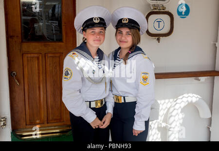 Russia, Vladivostok, 07/28/2018. Portrait of two young beautiful ladies sailors in official marine uniform on the deck of the sailboat. Concept of mar - Stock Photo