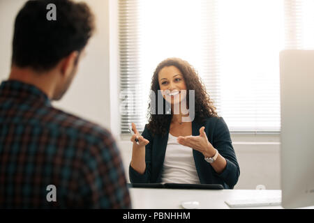 Woman entrepreneur discussing business ideas with a business partner in office. Businesswoman in a meeting with a businessman at her desk in office. - Stock Photo