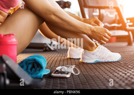 woman tying trainers in the gym close up - Stock Photo