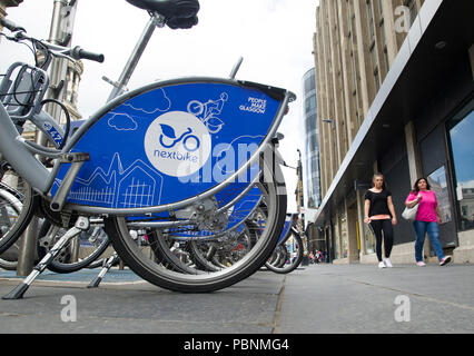 Nextbike bicycles for rent  lined up on a stand in Glasgow city centre. - Stock Photo