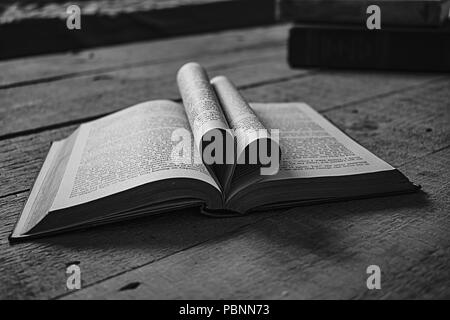 Old book, heartshaped pages open in the middle on a wooden table, perfect for inspirational or magical quotes. - Stock Photo