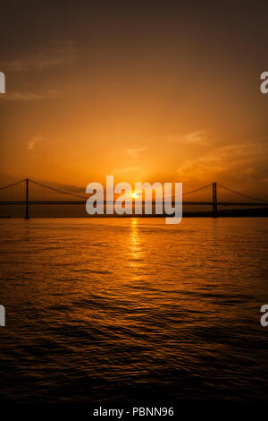 Ponte 25 de Abril - 25th of April Bridge on Tagus river at sunset, between Lisbon and almada, Portugal - Stock Photo