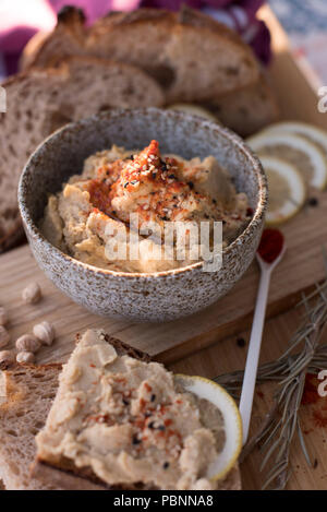 Hummus with wholemeal sourdough bread, paprika and lemon - Stock Photo