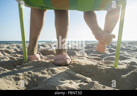 Little brothers sitting on beach chair in front of the sea. Low angle view - Stock Photo