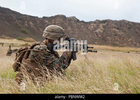A U.S. Marine 3rd Battalion, 3rd Marine Regiment, III Marine Expeditionary Force, provides suppressive fire with is M27 Infantry Automatic Rifle during a fire team assault at the Kaneohe Bay Range Training Facility, Marine Corps Base Hawaii, July 26, 2018. Riflemen utilized their individual weapon systems such as the M203 Grenade Launcher, M72 Light Anti-Tank Weapon (LAW), M4A1 Assault Rifle and the M27 Infantry Automatic Rifle to conduct a fire team assault. Marines with India, Kilo and Limo Company worked together to improve their communication, leadership and lethality as a fire team. (U.S. - Stock Photo