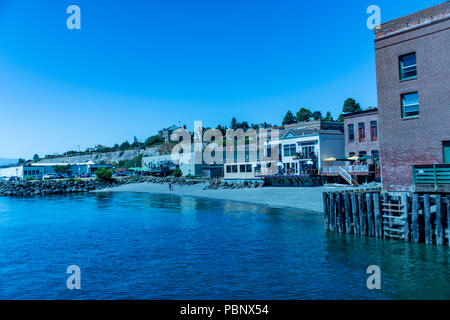 Waterfront view of old Victorian era architecture on a clear sunny day with blue sky.  Port Townsend, northwest USA. - Stock Photo