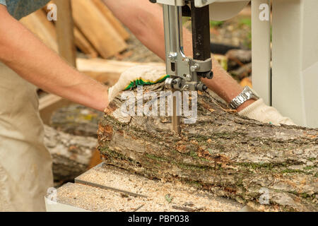 On a photo work of the carpenter cutting a tree on the woodworking machine. - Stock Photo