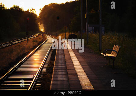 Late afternoon sunlight reflects off train tracks next to the platform at the small train station of Quelle, near Halle (Westfalen), Germany. - Stock Photo