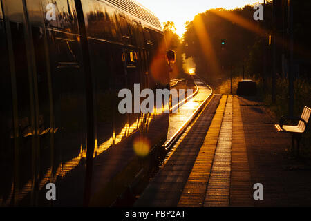 Late afternoon sunlight reflects off a train arriving at the small train station of Quelle, near Halle (Westfalen), Germany. - Stock Photo