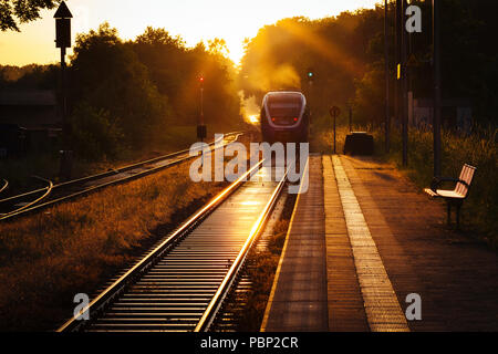 Late afternoon sunlight reflects off train tracks next to the platform as a train leaves the small train station of Quelle, near Halle (Westfalen), Ge - Stock Photo