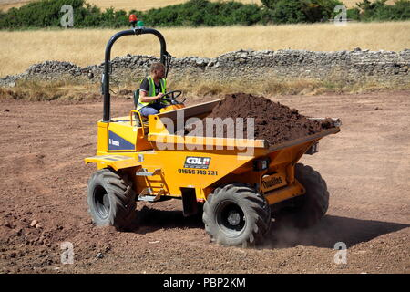 A skilled tipper truck driver moves his full load of earth into position before tipping it in place during restoration works. - Stock Photo