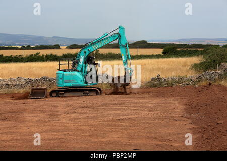 A newly commisioned large tracked digger levelling off the earth in a newly restored field before being returned to the farmer. - Stock Photo