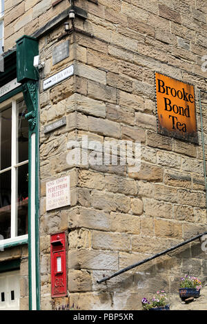 Corner of the old Post Office building in King Street, Robin Hood's Bay, showing post box and enamel Brooke Bond tea advertising sign - Stock Photo