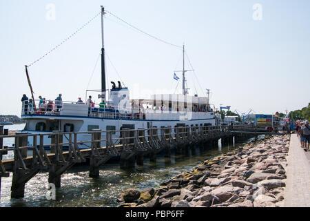 Warnemunde, Germany - June 8, 2018: Tourist sightseeing boat at dock loading passengers - Stock Photo