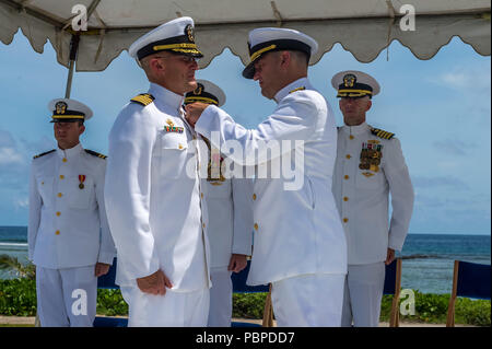 180719-N-WG252-098 ASAN BEACH, Guam (July 19, 2018) Rear Adm. Troy McClelland, Deputy Commander for the Naval Construction Force, Navy Expeditionary Command, presents Capt. Jeffrey Kilian with a Legion of Merit for his accomplishments as commodore of the 30th Naval Construction Regiment during the regiment's change of command ceremony at the War in the Pacific National Historical Park Asan Beach Unit. During the ceremony, Capt. Steven Stasick relieved Kilian as commodore of 30 NCR. (U.S. Navy photo by Chief Mass Communication Specialist Matthew R. White /released) - Stock Photo