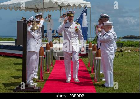 180719-N-WG252-244 ASAN BEACH, Guam (July 19, 2018) Capt. Steven Stasick, commodore of the 30th Naval Construction Regiment, salutes sideboys following 30 NCR's change of command ceremony. Stack relived Capt. Jeffrey Kilian during the ceremony at the War in the Pacific National Historical Park Asan Beach Unit. (U.S. Navy photo by Chief Mass Communication Specialist Matthew R. White /released) - Stock Photo