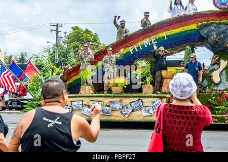 180721-N-WR252-111 AGANA, Guam (July 21, 2018) Sailors assigned to the 30th Naval Construction Regiment (30 NCR) participate with the Village of Barrigada's and ride on their float during the 74th Anniversary celebration of Guam's Liberation Day. The Battle for Guam began July 21, 1944, when American forces invaded Guam to liberate it from the Japanese occupiers. Barrigada is 30 NCR's Sister Village, which is a partnership between the village and command for community service and outreach opportunities. (US. Navy photo by Chief Mass Communication Specialist Matthew R. White /released) - Stock Photo