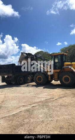 80719-N-ZH657-4031 ANDERSEN AIR FORCE BASE, Guam (July 19th, 2018) Seabees, assigned to Naval Mobile Construction Battalion (NMCB) 11, Detachment Guam, use a front end loader to load a dump truck with select fill for transportation.  NMCB-11 is forward deployed to execute construction, humanitarian and foreign assistance, and theater security cooperation in the 7th Fleet area of operations. (U.S. Navy photo by Construction Mechanic 2nd Class Brittney Ebbert) - Stock Photo