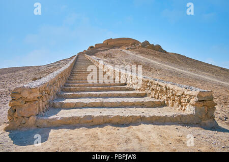 The long stone staircase leads to the hilltop, ending with ancient Zoroastrian burial structure - Tower of Silence (Dakhma), Yazd, Iran. - Stock Photo