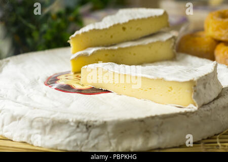 Close up of cut brie cheese sold on a Paris market, France. - Stock Photo