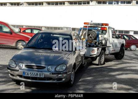 An illegally parked car  being towed away by a pick-up tow truck in Cadiz,  Andalusia, Cadiz-province, Spain - Stock Photo