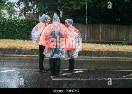 London UK. 29th July 2018. Race stewards dressed in  rain ponchos for the Prudential London Surrey 100 classic event in wet conditions as the rains come down. The Prudential ride Celebrates  the legacy for cycling created by the London 2012 Olympic and Paralympic Games and follows a 100-mile route on closed roads through the capital and into Surrey's  countryside Credit: amer ghazzal/Alamy Live News - Stock Photo