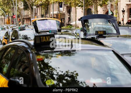 Hundreds of parked taxi vehicles collapse the Gran Via avenue in downtown Barcelona, northeastern Spain, 29 July 2018, during the fifth day of a taxi strike. The taxi drivers protest in defense of the Barcelona's metropolitan area regulation which provides one local license for VTC (Tourism Vehicles with Driver) vehicle, from companies like Uber o Cabify, out of each 30 licenses for taxis. This regulation has been preliminarily suspended by a court after it was accepted an appeal by Spanish National Market and Competition Commission. EFE/Alejandro Garcia - Stock Photo