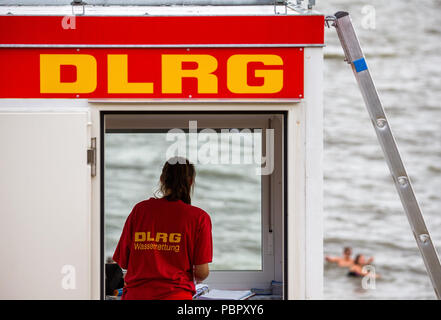 29 July 2018, Germany, Wilhelmshaven: A lifeguard of the DLRG (Deutsche Lebens-Rettungs-Gesellschaft) stands in front of the window of a watch tower on the southern beach. Photo: Mohssen Assanimoghaddam/dpa - Stock Photo