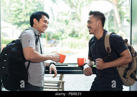 Side view of two cheerful young men talking and drinking coffee  - Stock Photo