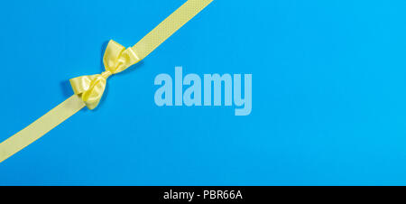 Yellow polka dot ribbon bow packaging gifts on blue background - Stock Photo
