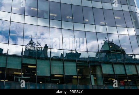 Reflections of decorative ironwork of old buildings in modern glass office building windows, Ingram Street, Glasgow, Scotland, UK - Stock Photo