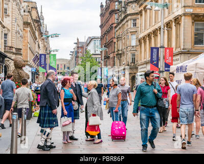 People dressed for a wedding with men in kilts stopping to say hello and greeting each other in a busy street, Buchanan Street, Glasgow, Scotland, UK - Stock Photo