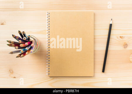 Design concept - Top view of kraft spiral notebook, pen holder and wood pen on wooden table background for mockup - Stock Photo